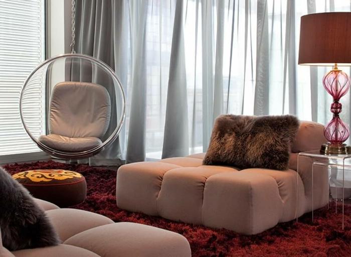 bordeau couleurn chaise oeuf suspendue, sofas bas en beige crémeux, tables acryliques gigognes et lampe rouge