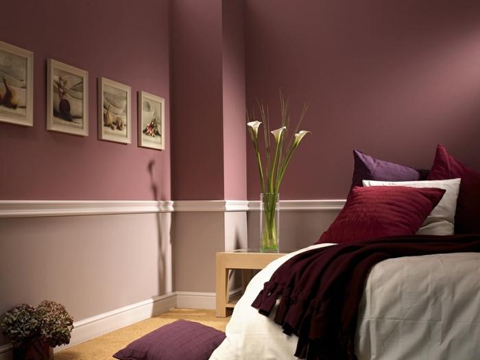 lie de vin couleur, coussins déco, plusieurs tableaux peintures, vase avec bouquet sur un chevet en bois