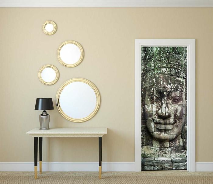 couleur zen, deco salon zen, porte décorée de sticker mural style ethnique avec visage d'aztèque, table rectangulaire avec surface en blanc et des pieds noirs avec des extrémités en bois clair, luminaire sut table avec abat-jour noir et base en couleur argent