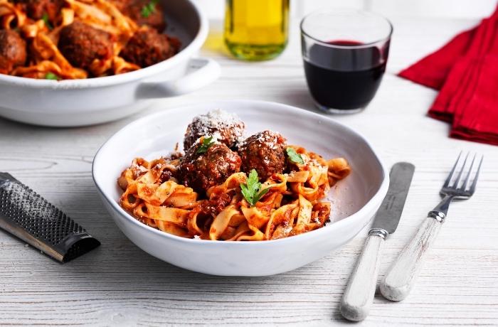 idée repas convivial entre amis, spaghettis aux boules de viande hachée à la sauce tomate servis avec basilic et parmesan