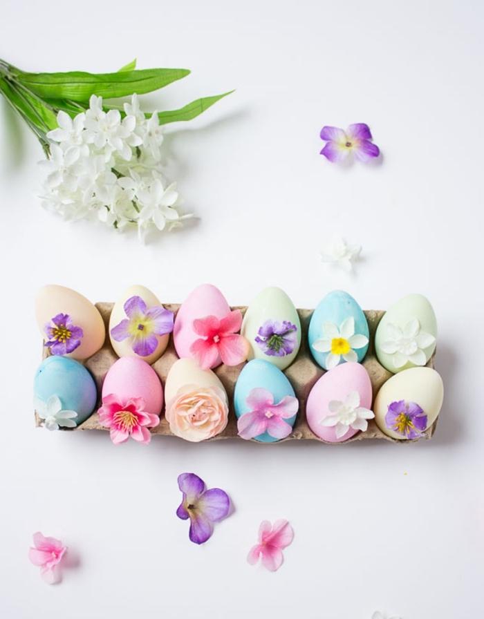 exemple d'oeufs colorés en nuances pastel et décorés avec petites fleurs en rose et violet, modèle de déco romantique et douce