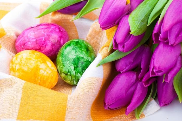 déco de paques avec bouquet de tulipes violet et panier en serviette blanc et jaunes avec oeufs colorés à design marbré