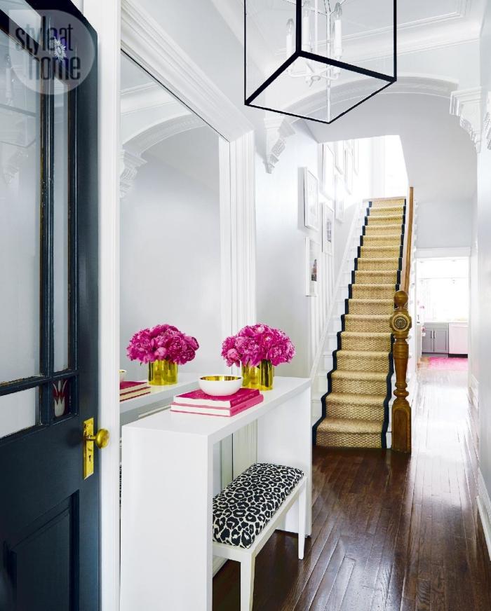 idée déco de couloir blanc avec porte noire et escalier en bois avec tapis doré et noir, meubles d'entrée en blanc