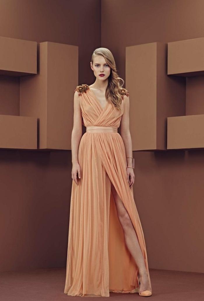exemple de robe de soirée chic de longueur sol avec décolleté en v et ceinture, modèle de robe de couleur orange pastel avec fleur 3D sur épaule