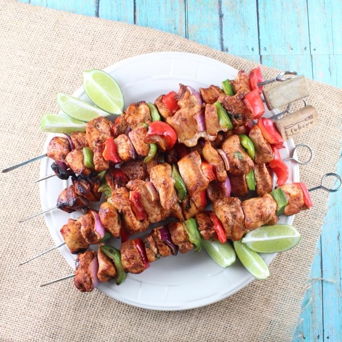 brochettes à la viande et poivrons vertes et rouges à garnir avec morceaux de citron vert pour un repas du soir entre amis