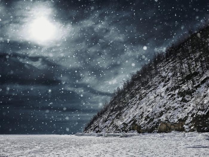 fond ecran paysage hivernal avec tempête de neige au-dessus des champs, colline enneigé et ciel gris et noir