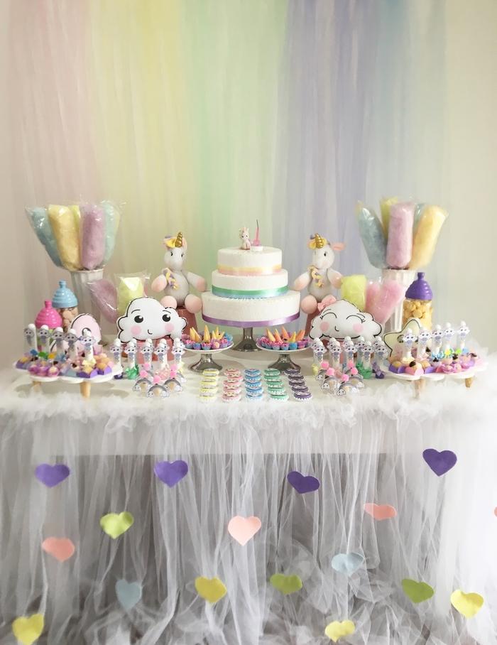 jolie déco de buffet de desserts revêtu d'une jupe de table en tulle personnalisée avec des coeurs en papier pour un anniversaire licorne à inspiration kawaii tout en délicatesse