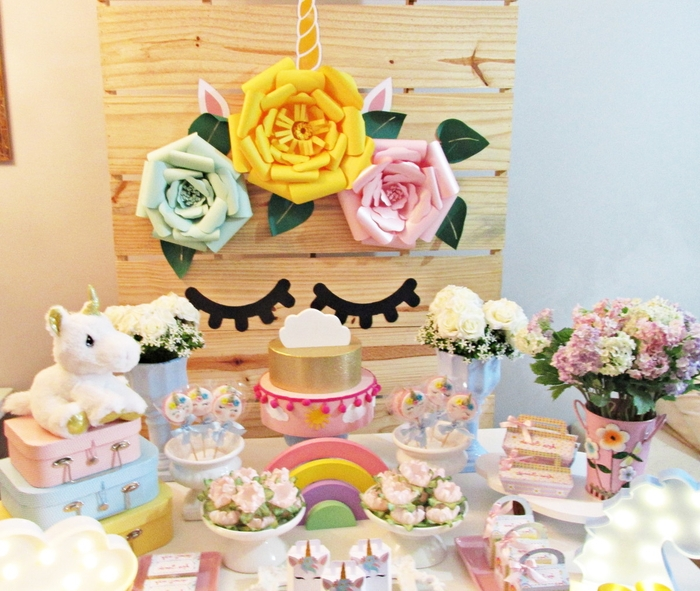 déco de buffet d'anniversaire licorne en tons pastel et fleurs sur un arrière-plan en bois personnalisé avec des fleurs en papier et des stickers yeux fermés