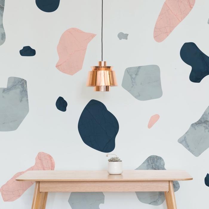 intérieur stylé avec papier peint moderne blanc à design terrazo gris et rose poudré avec meubles de bois clair et lampe cuivrée