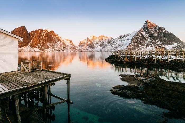 photo de montagne enneigée avec pont et cabine de bois au bord d'un lac, coucher de soleil dans la nature