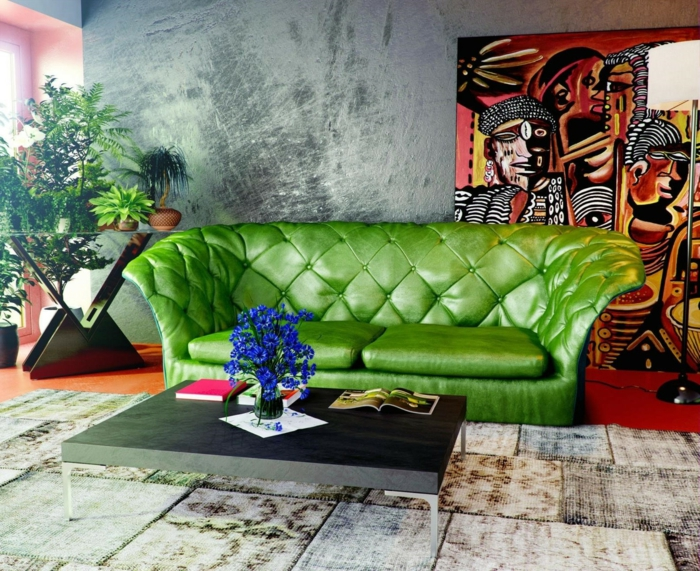 déco murale béton ciré, panneau mural bariolé en teintes rayonnantes, canapé vert, tapis patchwork, table basse moderne