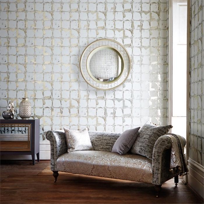 ambiance luxueuse dans un salon aménagé avec meubles beige et une déco murale en papier peint blanc et or