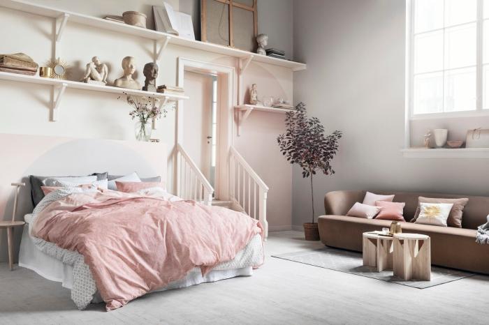 aménagement studio avec peinture rose pale et beige, rangement mural avec étagères de bois, modèle de canapé marron avec table basse