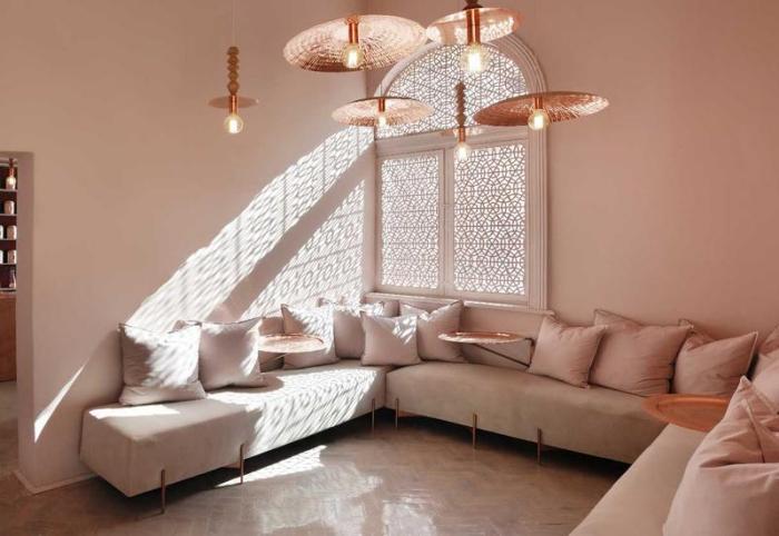 idée aménagement d'un salon avec canapé d'angles et coussins rose pastel, exemple peinture rose poudré dans le salon