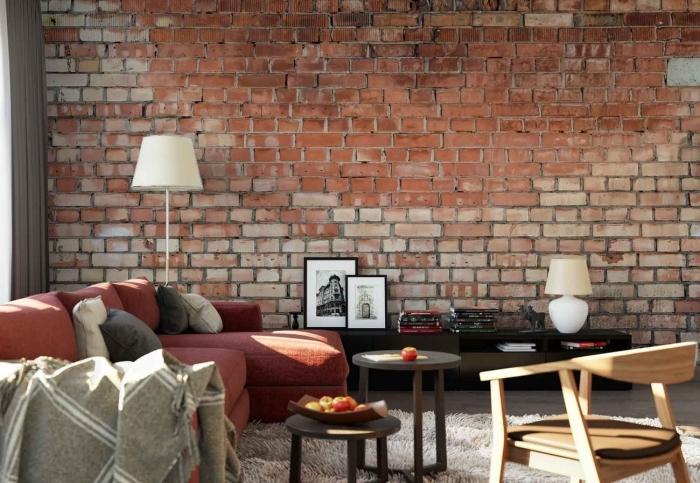 aménagement de salon en style industriel avec décoration murale en papier peint brique et meubles de bois en noir mate