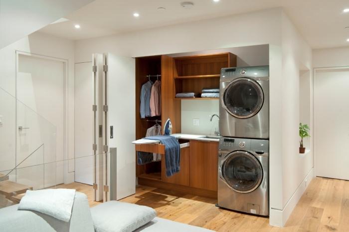 modèle de deco buanderie aux murs blancs et parquet de bois avec éclairage led du plafond et meubles de bois foncé