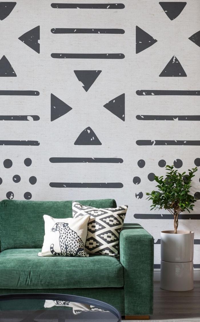 déco minimaliste avec papier peint noir et blanc aux motifs géométriques et modèle de canapé vert couvert de coussins blanc et noir