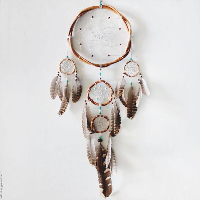 modele d attrape reve fabrication à partir de cercles de branches de bois marron, decoration de plumes et perles marron et bleus