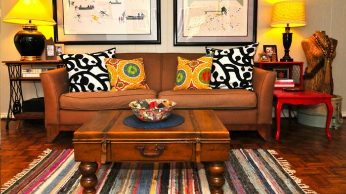 table basse valise vintage, sofa marron, chaise rouge baroque, deux chevets avec lampes abat-jour, tableaux peintures