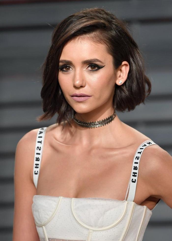 look chic et moderne de nina dobrev avec une coupe de cheveux carré plongeant wavy et une frange portée sur le côté