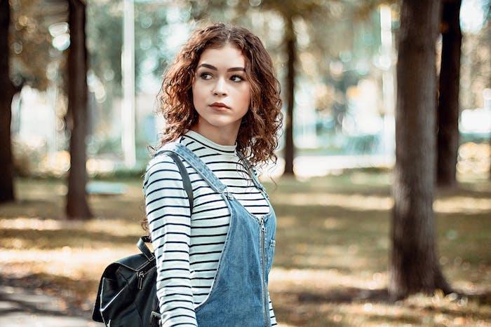 cheveux bouclés femme, ondulations rebelles sur un carré mi long chatain, salopette en jean, chemise à rayures noir et blanc