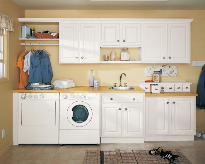 deco buanderie chaleureuse aux murs jaunes et carrelage de plancher beige avec cintres pour vêtements et étagères pour produits de nettoyage