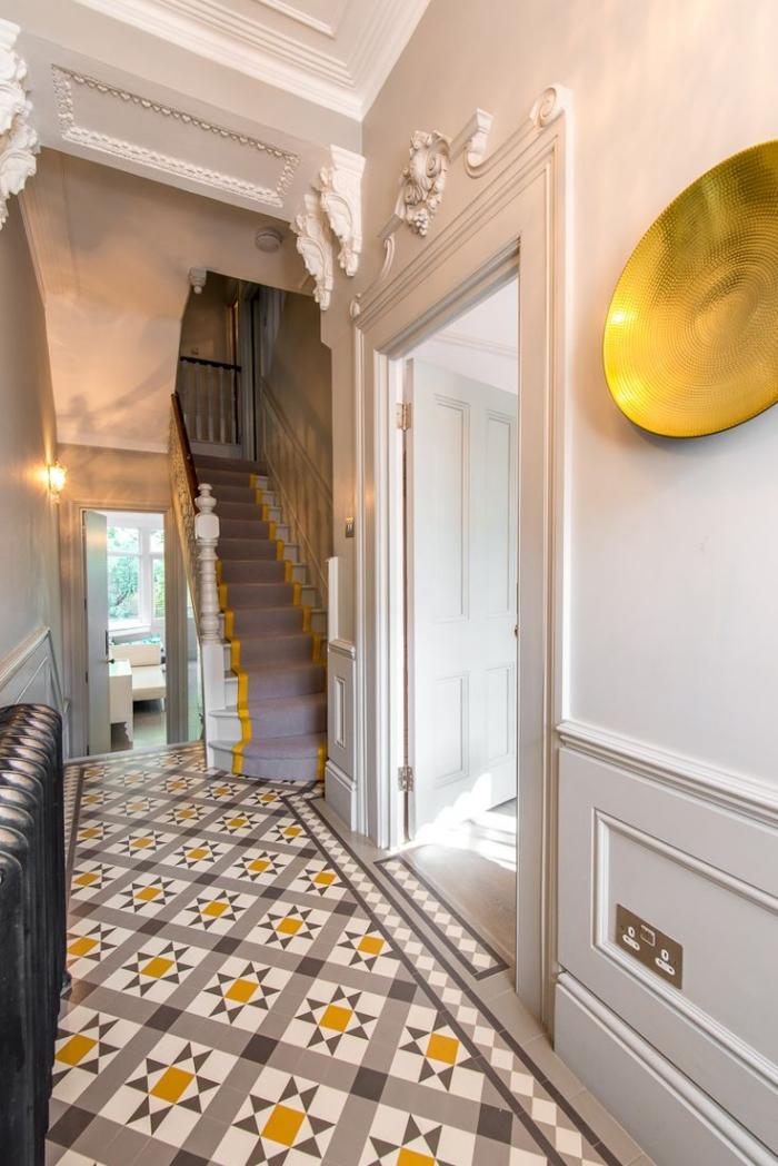 intérieur avec décoration murale et plafond de plâtre aux motifs volutes et géométriques, modèle de carrelage gris et blanc