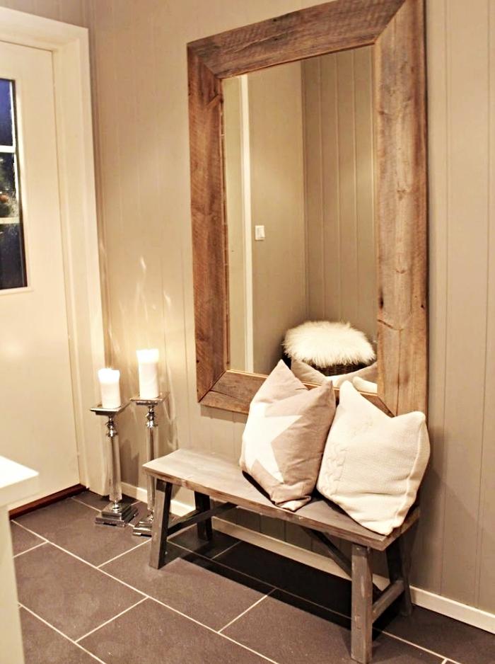idée déco chaleureuse de couloir avec banc et miroir de bois décorés de coussins beige et bougeoir à design métallique