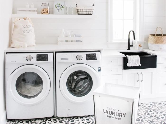 amenagement cellier avec machines à laver sur plancher au carrelage blanc et noir, évier noir matte combiné avec armoires blanches