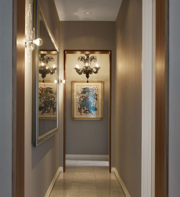 aménagement de couloir long et étroit aux murs gris clair avec grand miroir et lustre baroque, modèle de carrelage plancher en beige