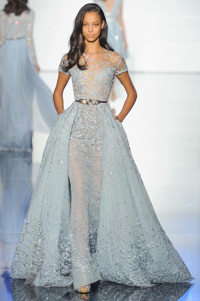 modèle robe de soirée tendance de couleur bleu pastel avec jupe à volants et déco florale sur le haut transparente