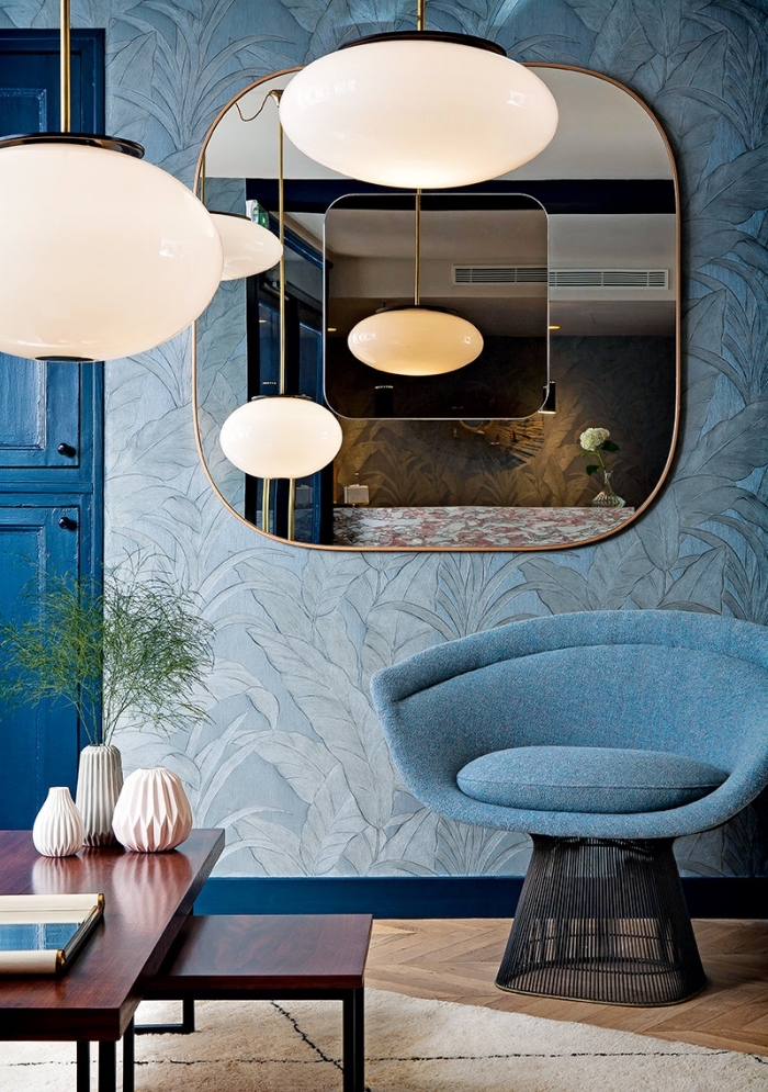 salon aux murs habillés en papier peint moderne de couleur bleu clair, déco de salon au plancher de bois et meubles bleus
