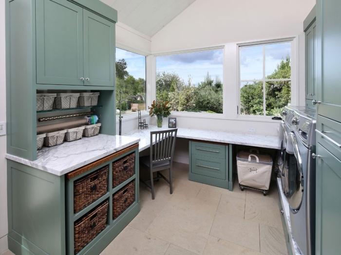 meubles de bois peints en vert combinés avec comptoir blanc pour un aménagement buanderie de style vintage et de look moderne