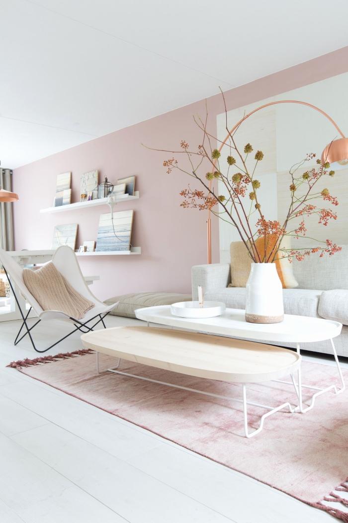 salon au plafond et parquet blanc avec peinture rose pale sur les murs, meubles blancs et bois sur un tapis rose poudré avec franges