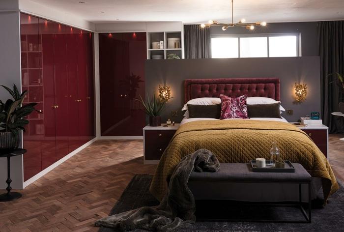 peinture murale rouge bordeaux, plaid de lit vert curry, banquette de lit grise, parquet chevron