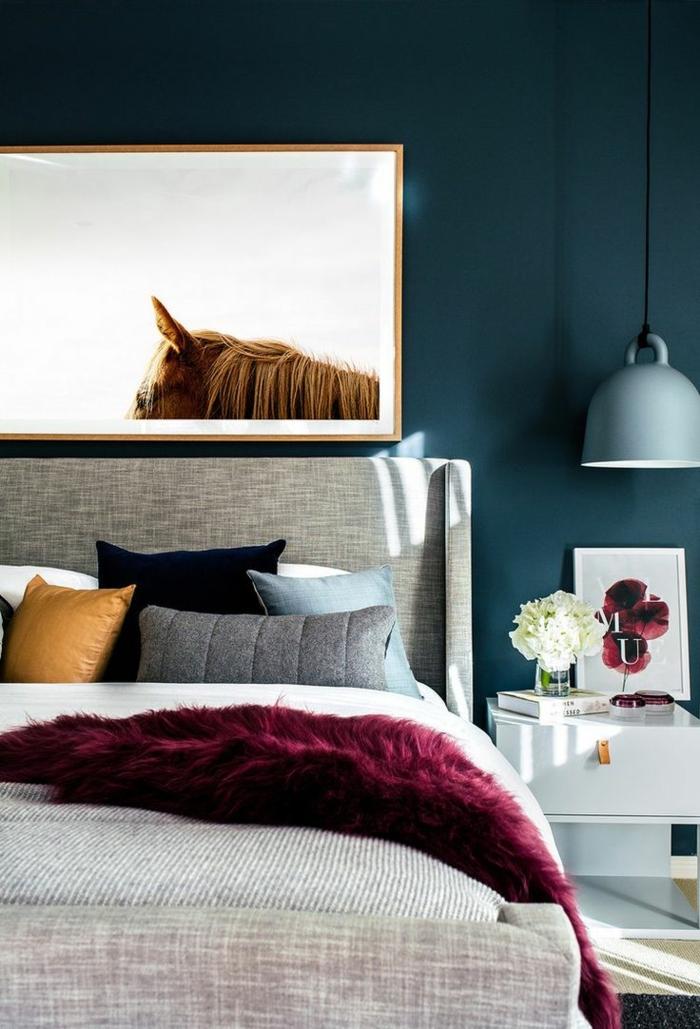 couleur peinture bleue pétrole, photo artistique, plaid moelleux couleur vineuse, lampe industrielle, petit chevet blanc