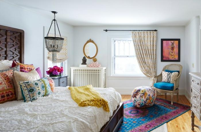 tapis vintage en bleu et rose, lit avec plusieurs coussins, plafonnier oriental, pouf en couleurs joyeuses
