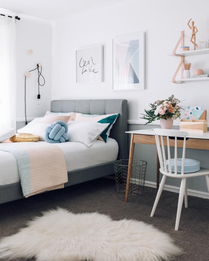 amenagement chambre à coucher moderne au design scandinave épuré en tons pastel avec un coin bureau près du lit et un coussin à noeud tendance