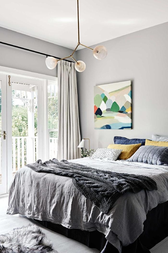 idée deco pour chambre à coucher grise égayée par un tableau en couleurs vitaminées et quelques coussins décoratifs en bleu et jaune moutarde