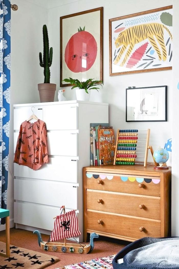 deco chambre fille, pot avec cactus posé sur un meuble rangement haut et blanc, petit meuble en bois clair, rideaux en bleu et blanc, tapis en noir et beige et tapis en couleurs pastels, deux tableaux en cadres marrons, un tigre et une tomate toute rouge