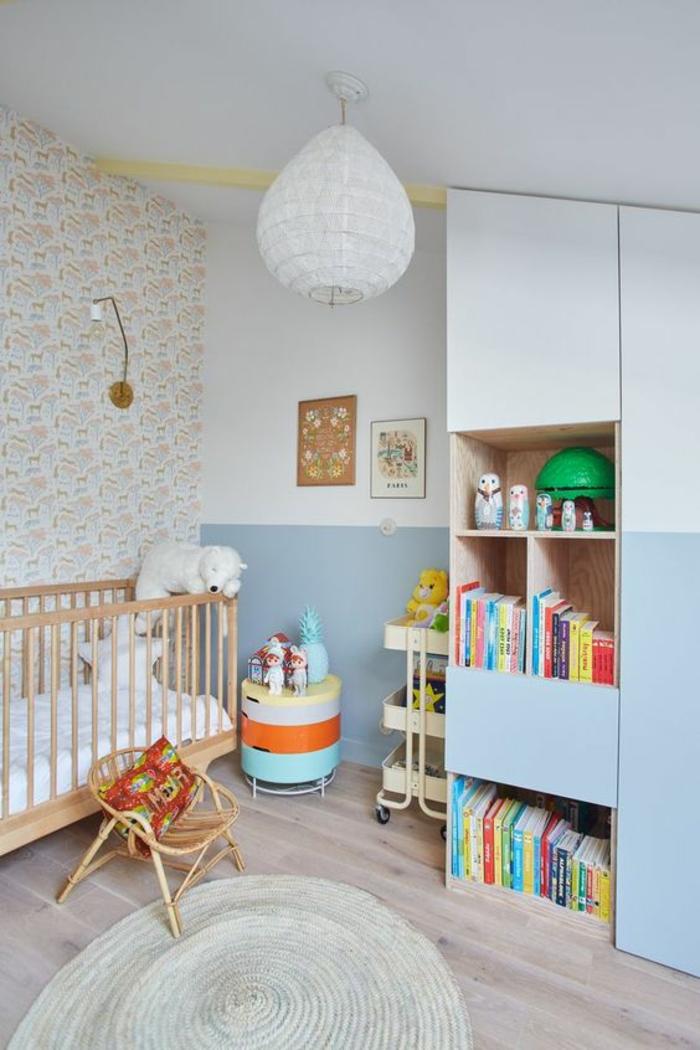 cadre chambre bébé, mur blanc, lustre chambre, tapis rond tressé, meuble moitié blanc, moitié en bleu pastel, parquet en gris, lit bébé en bois clair