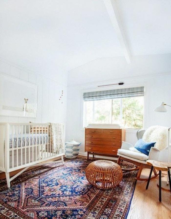 chambre gris et blanc, tapis oriental en bleu roi et bordeaux, tabouret rond en osier style pouf, lit blanc, murs blancs, meuble vintage en bois clair, fauteuil bascule en tissu blanc avec des pieds en bois clair