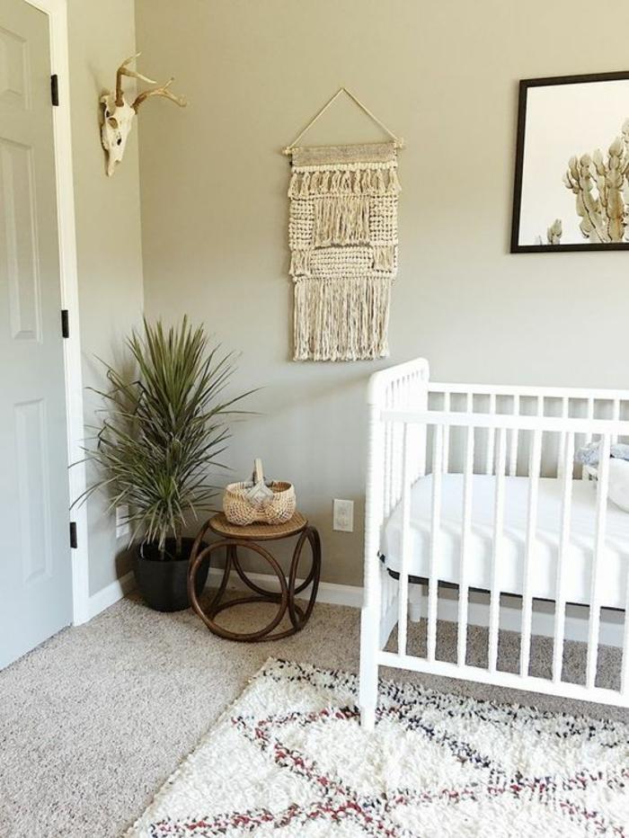 décoration chambre bébé fille, lit bois peint en blanc, murs en gris clair, petite table basse en rotin marron, tapis aux motifs losanges en blanc, rouge et bleu