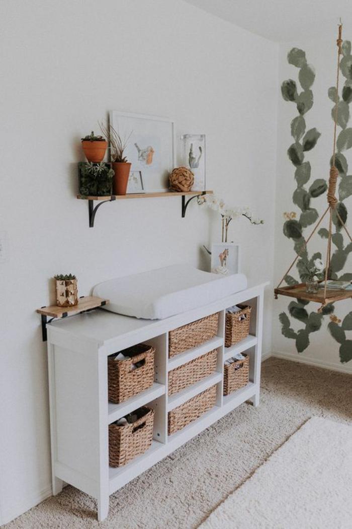 meuble de rangement blanc avec des paniers carrés de rangement en osier, petit matelas pour changer les pampers de bébé sur le meuble blanc, murs en blanc avec des cactus verts peints, étagère en fer forgé et en bois clair