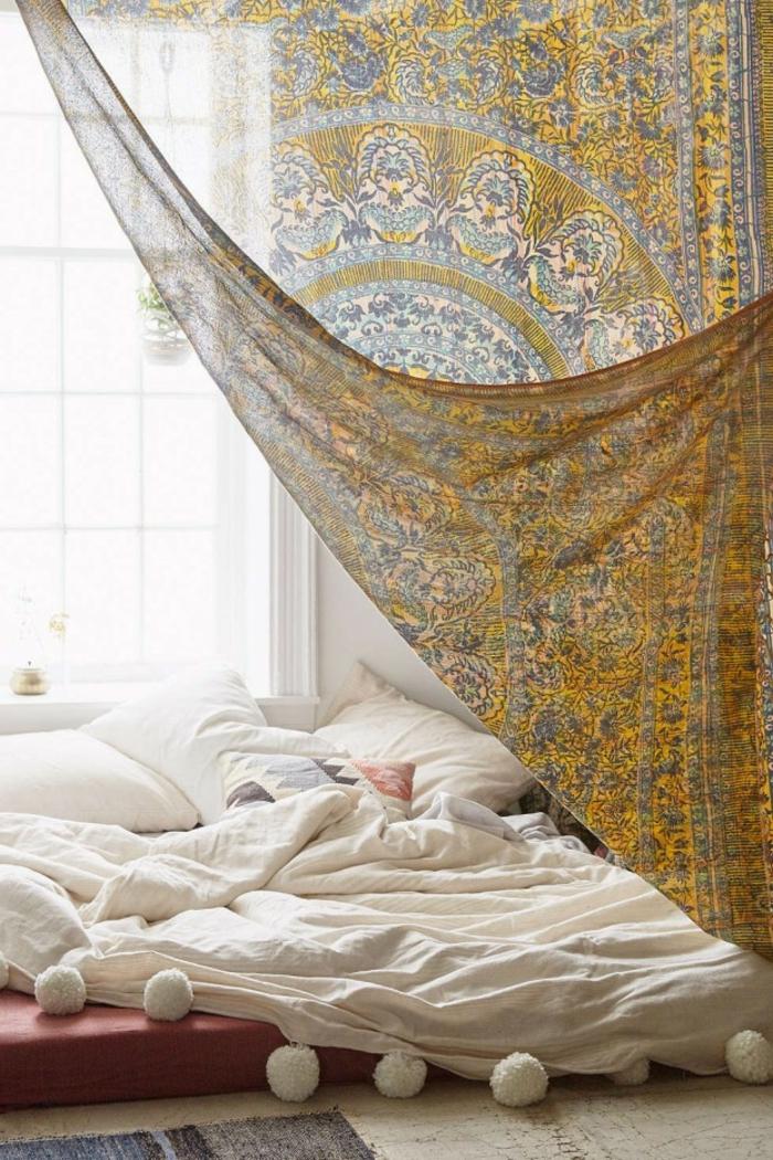 lit bas tout près du sol, baldaquin ethnique, coussins blancs, couverture de lit blanche