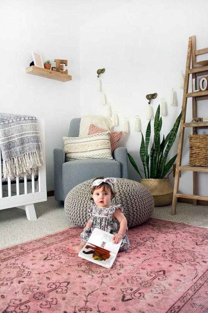 chambre gris et blanc avec un tapis rose aux ornements en noir, échelle avec des casiers et avec le nom de l'enfant