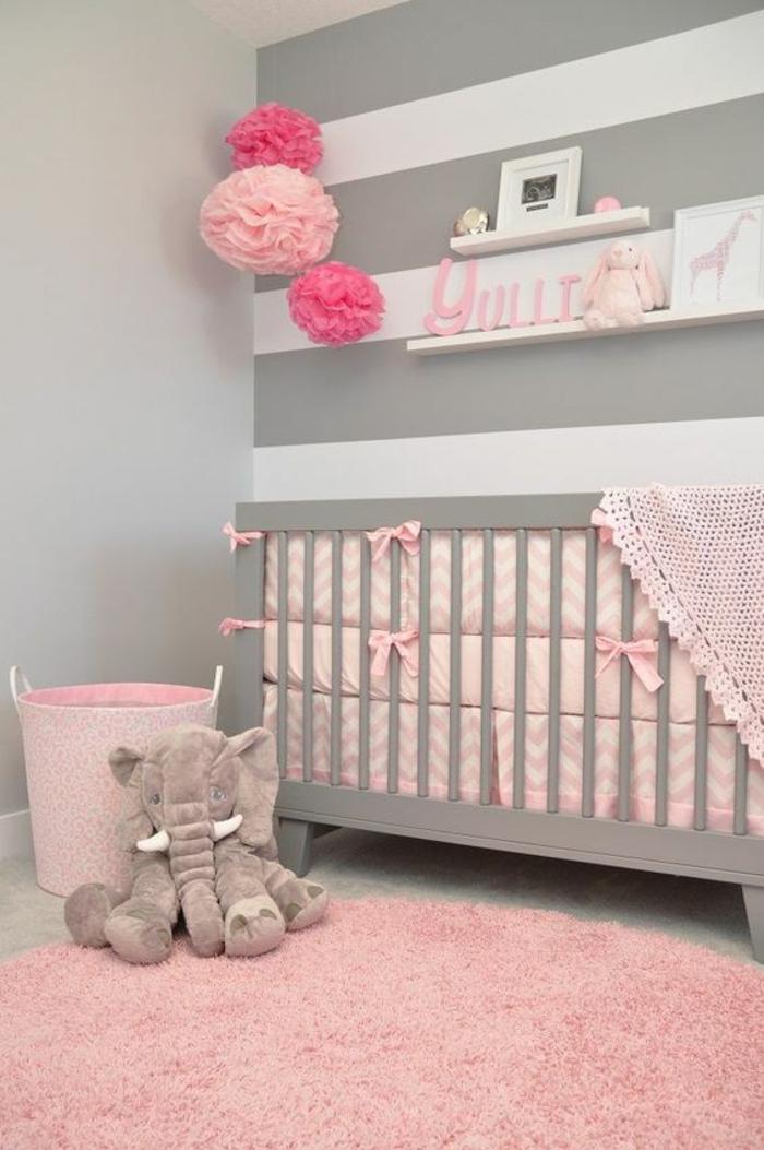 grand tapis rond rose, mur avec des rayures horizontales grises et blanches, lit en gris pastel, linge de lit en rose, des pompons en carte rose et fuchsia suspendus au-dessus du lit, éléphant gris en peluche, étagères blanches