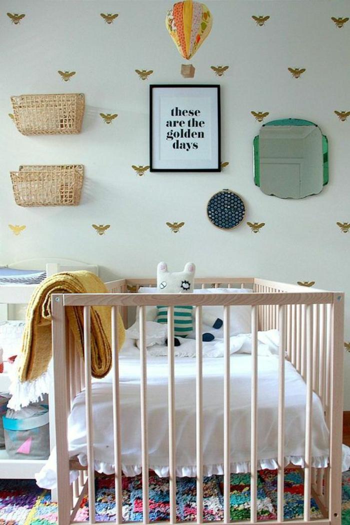les journées heureuses, murs blancs avec des abeilles en couleur or, montgolfière en jaune et orange suspendue au plafond, lit en bois clair, étagères murales conteneurs en canne tressée