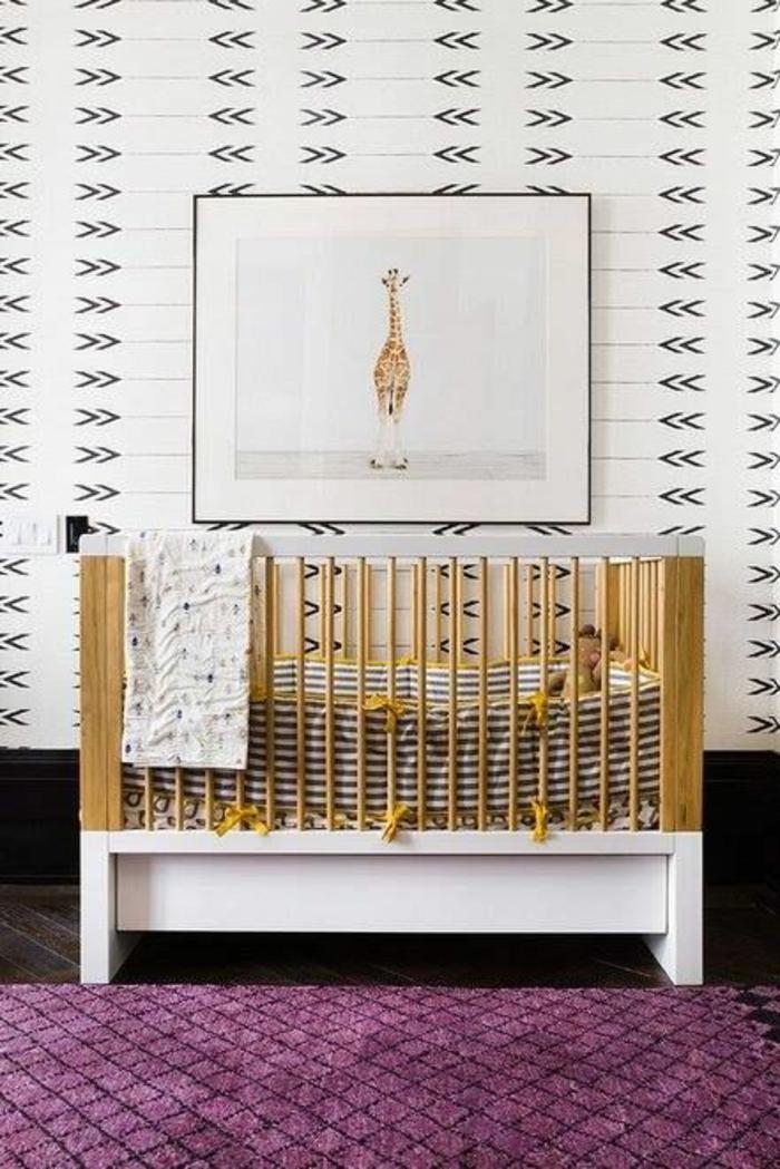 tableau avec image de girafe en cadre noir fin au-dessus du lit en couleur jaune et blanc, tapis fuchsia au mini-losanges noirs, mur en blanc avec des motifs graphiques noirs