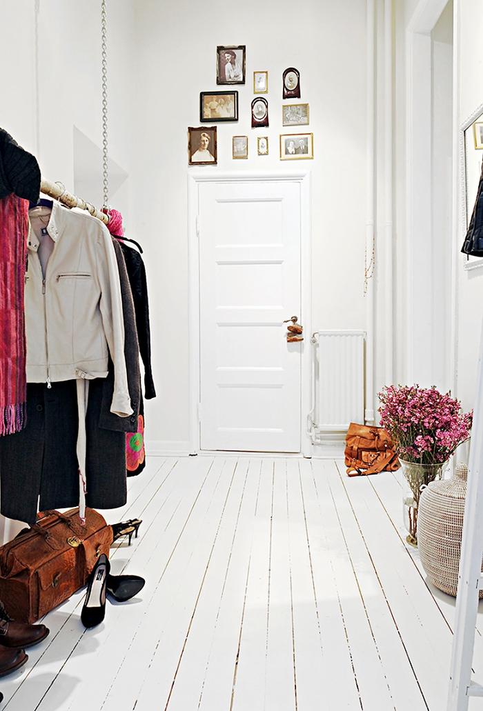 idée déco entrée maison en style femme avec murs blancs et parquet de bois peint blanc, porte-manteau et coffre marron